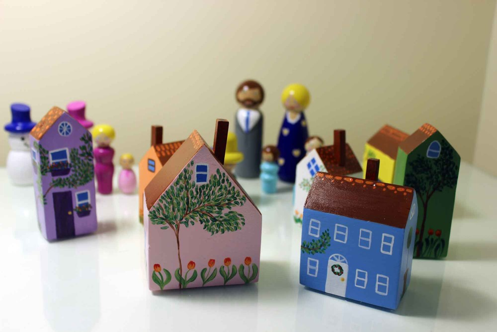 Painted wooden houses with peg dolls.